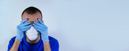 The doctor covers his face with his hands in gloves in a protective mask and blue clothes on a blue background. He is afraid of infection and does not know what to do and how to be.copyspace for text