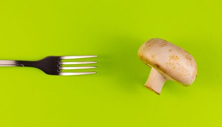 The fork is directed towards the champignon on a green background. Top view .copyspace for text