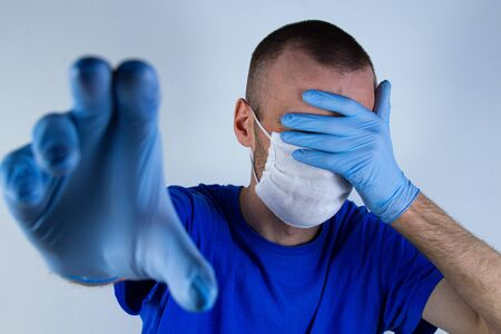 A young man covers his face with a glove in a protective mask. A hand shows a stop in blue clothes on a blue background Zdjęcie Seryjne