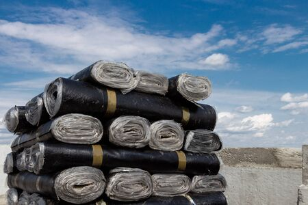 A close-up of rolls of new black roofing felt or bitumen that is precisely folded against a blue sky Archivio Fotografico