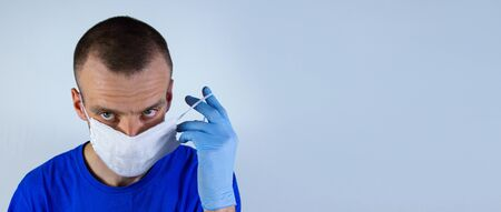The doctor puts a mask on his face with a gloved hand in blue clothes on a blue background. He is afraid of infection and does not know what to do and how to be. He looks forward confidently sternly.copyspace for text.