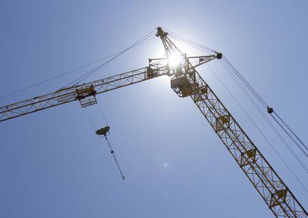 A crane at a construction site raises a hook. Against the background of blue sky and bright sun. Zdjęcie Seryjne