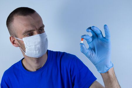 Young man in a protective mask and blue clothes on a blue background. He looks at the red capsule that he holds in his gloved hand