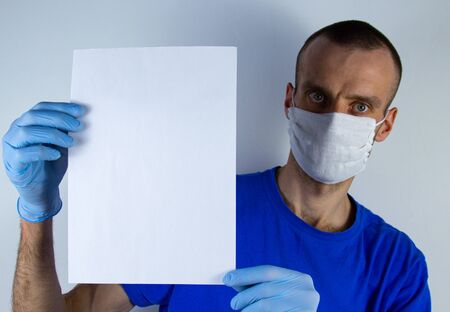 man in a protective mask on a blue background. holds a sheet of white paper vertically. Copyspace for text