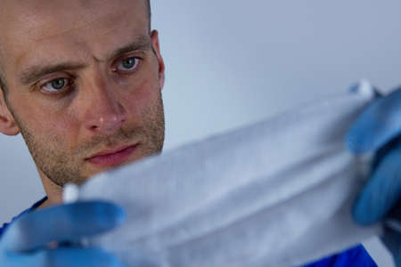 Doctor Muschina in gloves holds a medical mask on a white background. Help and Protection Concept