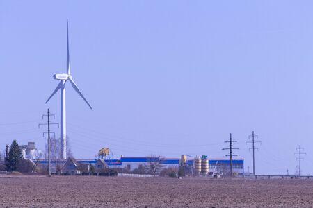 Wind generator far on the horizon, construction alternative energy production concept. Against the blue sky