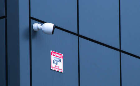 CCTV cameras are installed on the facade of a gray office building. Safety and warning concept. 写真素材