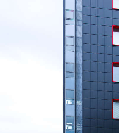 Corner of a building with many windows against a white sky. Concept of modern construction.