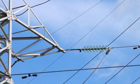 High voltage electric wires on a steel pole against a blue sky