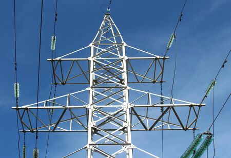 Steel pylon with high voltage electrical wires against a blue sky with clouds.