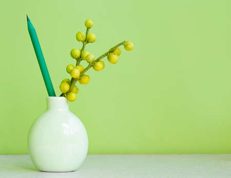pencil and flower in a vase on a green background.copyspace for text. 免版税图像