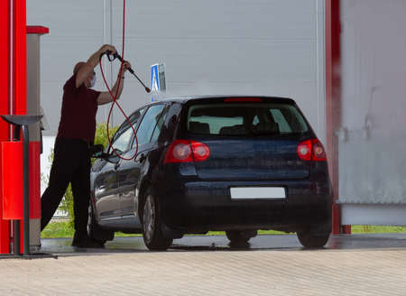 A man washes his car with a water pressure hose. Car service