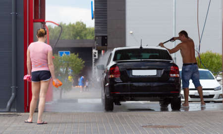 A man washes his car with a hose under the pressure of water. The woman is standing nearby. Car wash Imagens