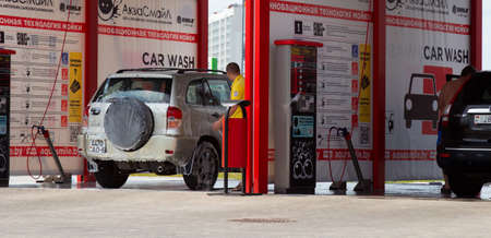 Self-service car wash in the open air. Man takes care of the car Imagens