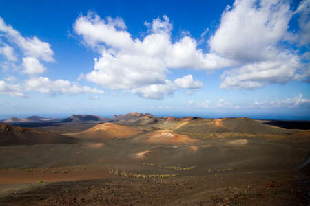 Panoramic view of Lanzarote volcanic island with blue cloudy sky