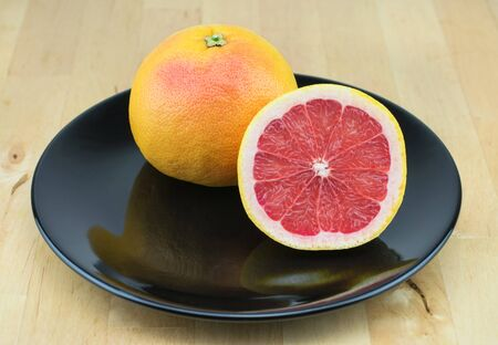 Juicy red grapefruit on the black plate.