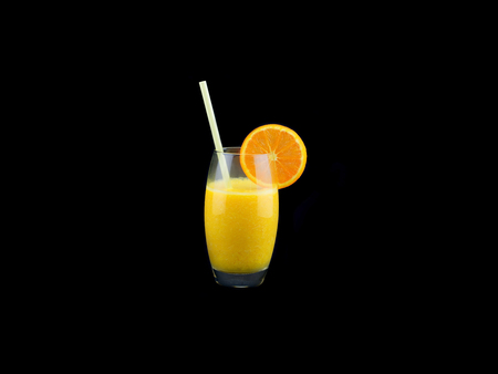 A glass with fresh orange juice isolated on black background