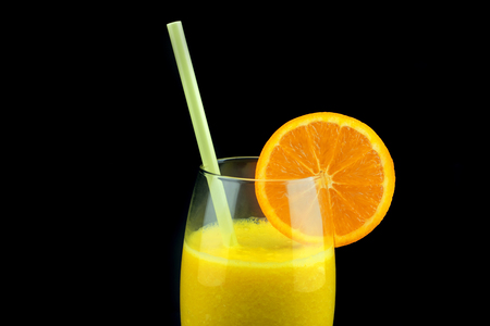 A glass with fresh orange juice isolated on black background. Natural fresh orange juice.
