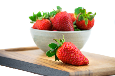 A bowl of ripe strawberry on the wooden board isolated on white background