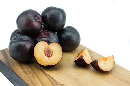 Ripe tasty plums on the wooden board, isolated on white background with clipping path
