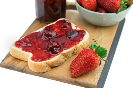 Bread with strawberry jam on a wooden board. Tasty breakfast , Ripe strawberries isolated on white background.  Stock fotó