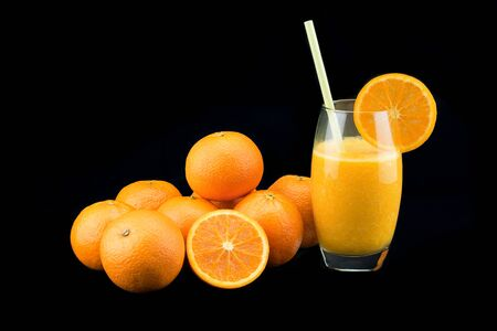 A glass of fresh orange juice with ripe orange heap isolated on black background Stock fotó