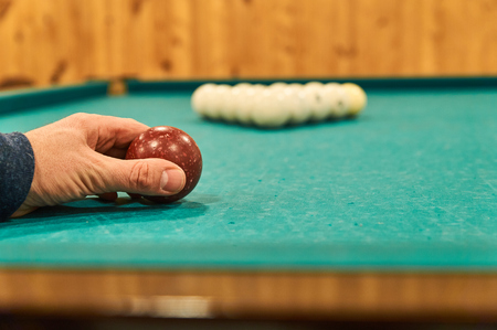 billiards halls: Man puts a ball to do a first blow in billiards game