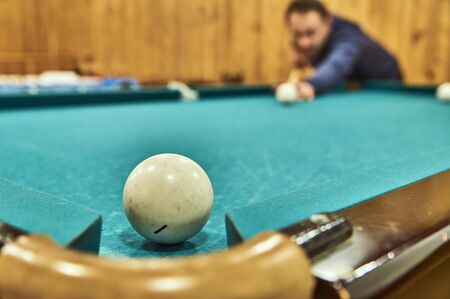 snooker halls: Middle-aged man playing billiards in the club.
