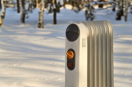 Oil filled radiator standing in snowy winter forest  Stock Photo