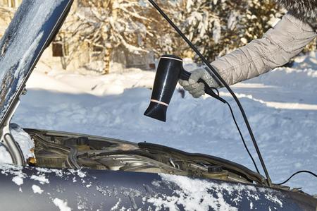 寒い冬の屋外でドライヤーを使用してモーターを温暖化の車の所有者