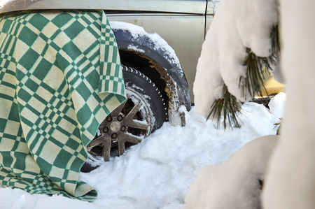 Warming up a diesel engine of suv car  by covering it with a woolen blanket Stock Photo
