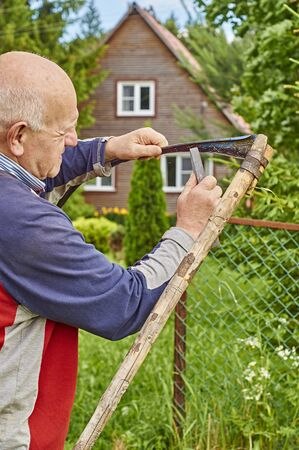 guadaña: Senior man sharpening a scythe before mowing the grass in front of his summer residence                                 Foto de archivo