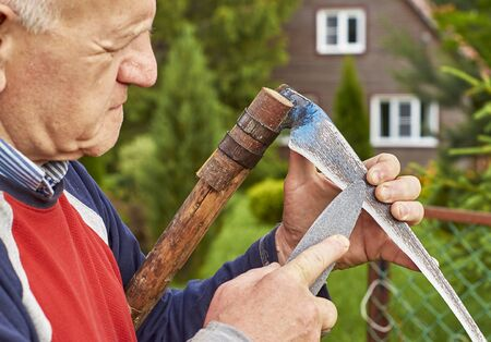 Senior man sharpening a scythe before mowing the grass in front of his summer residence                                 Stock Photo
