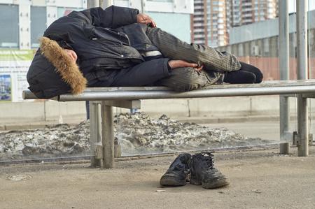 beggary: Male drunk beggar sleeping on bus stop