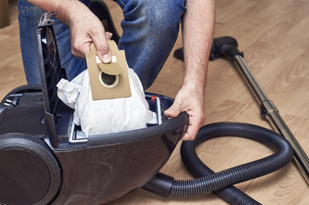 Removing full dust bag from a vacuum cleaner