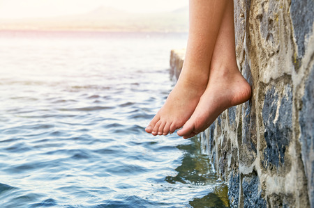 Wet bare girls feet dangling from the stone jetty