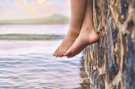 Natte blote meid's voeten hangend van de stenen pier