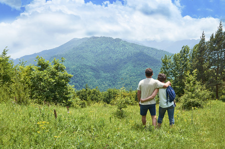 Middle-aged couple of tourists standing embraced and enjoying beautiful mountain view Stock Photo