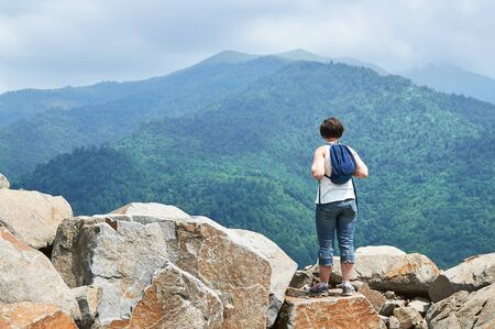 Female hiker standing on big stone on the top of the mountain and enjoying beautiful view Stock Photo