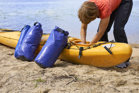 Female hiker inserting a waterproof bag with the things into the kayak Reklamní fotografie