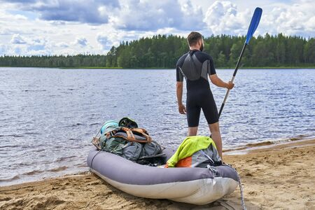 Young man standing on the lake shore holding a paddle ready to sail on the inflatable kayak