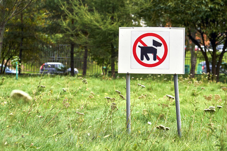 Warning sign forbidding dogs walking on the lawn Stock Photo