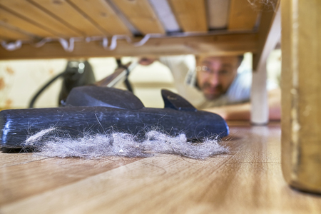 Man cleaning a floor under a bed with vacuum cleaner Stock Photo