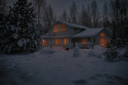 Country house covered with snow in cold winter night with lighted windows on Christmas Eve
