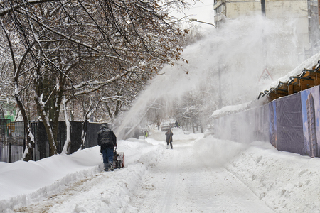 Municipal worker removing snow from the moscow street using snow blower after big snowfall 版權商用圖片