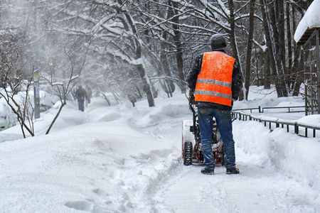 Municipal worker removing snow from the moscow street using snow blower