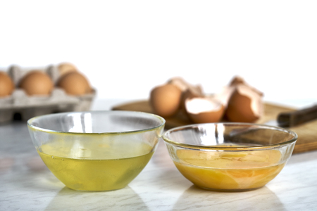 Transparent bowls with egg proteins and yolks