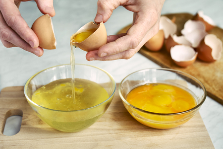 Woman separates a protein from a yolk