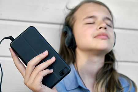 Teen girl with earphones listening and enjoying music from a smartphone Banque d'images