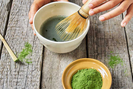 Matcha green tea accessoires on the rough wooden boards with girls hands preparing matcha tea in the special clay bowl Stockfoto